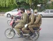 لاہور، شہر میں لاک ڈائون کے باعث ڈبل سواری پر پابندی کی خلاف کرتے ایک ..
