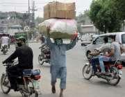 لاہور: ایک محنت کش سر پر بھاری وزن اٹھائے جارہا ہے۔