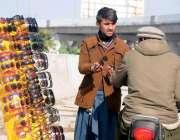 راولپنڈی: سڑک کنارے سٹال سے ایک موٹرسائیکل سوار دھوپ سے بچاؤ کی عینک ..