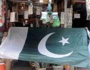 راولپنڈی : راجہ بازار میں ایک شہری بڑے سائز کا قومی پرچم پسند کر رہا ..