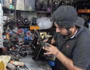 لاہور: ایک کاریگر سلائی مشین ٹھیک کر رہا ہے۔
