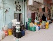 کراچی: لیاری نیازی چوک میں پانی کی قلت کے باعث خواتین خالی کین کے قریب ..