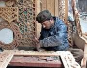 لاہور: ایک ورکر اپنے کام کی جگہ پر لکڑی کے فرنیچر پر مختلف ڈیزائن تیار ..