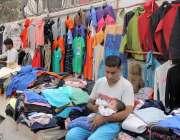 لاہور، میو ہسپتال روڈ پر قائم لنڈا بازار میں ایک سٹال ہولڈر اپنے بچے ..