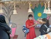 لاہور : جیلانی پارک میں جشن بہاراں فیسٹیول میں ایک خاتون اپنی بچیوں ..