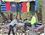 لاہور: ایک ٹریفک وارڈن دوران ڈیوٹی ریڑھی سے ٹی شرٹیں پسند کر رہا ہے۔