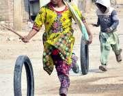 حیدرآباد: لطیف آباد میں سڑک پر پرانے ٹائروں کے ساتھ کھیلتے ہوئے بچے۔