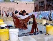 فیصل آباد: ایک لانڈری ورکر اپنے کام کی جگہ پر کپڑے دھونے میں مصروف ہے۔