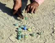 لاڑکانہ: رحمت پور محلہ کی گلی میں ایک بچہ بنٹوں سے کھیل رہا ہے