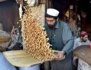 پشاور: کام کرنے کی جگہ پر ایک مزدور روایتی انداز میں مونگ پھلی کی صفائی ..