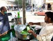 کراچی میں جاری شدید گرمی میں ایک ریڑھی والا ٹھنڈا مشروب فروخت کر رہا ..
