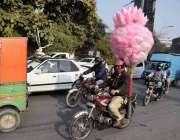 لاہور، ایک محنت کش موٹرسائیکل پر لچھے فروخت کرنے کیلئے لے جا رہا ہے۔