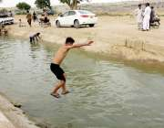 کراچی: گرمی کی شدت کے باعث بچے منگھو پیر کے علاقے سے گزرنے والی نہر میں ..