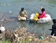 حیدرآباد: چینل موری کینال میں خود ساختہ کشتی پر بیٹھے بچے مچھلیاں پکڑ ..