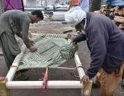 پشاور: مزدور روایتی چارپائی باندھنے میں مصروف ہیں۔