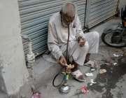 لاہور: ایک بزرگ حقہ پی رہا ہے۔
