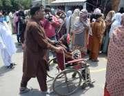 لاہور : ایک شہری معذور خاتون کو وہیل چئیر پر بٹھا کر نادرا کے دفتر لا ..
