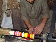 MULTAN:A worker busy in coloring parts of traditional bed (Charpai) at his workplace.