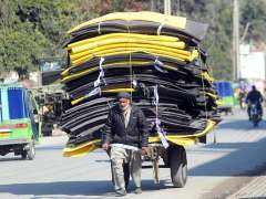 RAWALPINDI:An elderly labourer pulling a hand cart loaded with foam sheets to supply to market.
