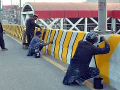 MULTAN:Labourers painting on the side wall of General Bus Stand Road.