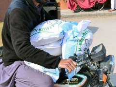 HYDERABAD:A motorcyclist on the way while carrying wheat flour bags after purchasing on government control rate.