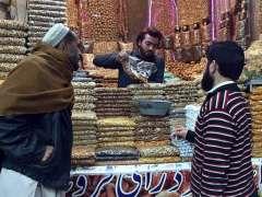 PESHAWAR:Customers selecting and purchasing dry fruits at Fawara Chowk.