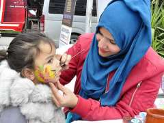 ISLAMABAD:A lady painting a visitor child's face during Smart Expo of Future Development at Pak-China Friendship Center.