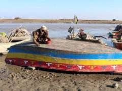 SUKKUR:A fisherman repairing his boat at the banks of Indus River near Zero Point.