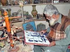 MULTAN:An artist busy in framework at craft bazaar.