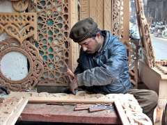 LAHORE:A worker carving different designs on wooden furniture parts at his workplace.