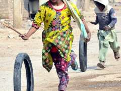 HYDERABAD:Children playing with old tyres on the road at Latifabad.