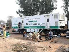 MULTAN:People waiting for treatment while near mobile health unit organized by Punjab Health Facilities and Management Company Hamidpur Kanora.