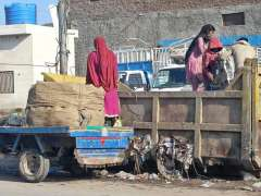 MULTAN:Gypsy family searching valuables from garbage container.