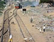 کراچی، بلوچ کالونی کے قریب ٹریک کے گرد لوگ گزر رہے ہیں جبکہ ایک تیز ..