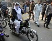لاہور، ایک موٹرسائیکل سوار خاتون اپنی منزل کی جانب گامزن ہے۔