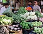 کراچی، لی مارکیٹ میں شہری سبزیاں خرید رہے ہیں۔