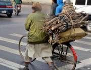 لاہور، ایک محنت کش جلانے کیلئے لکڑیاں سائیکل پر رکھے جا رہا ہے۔