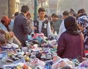 کراچی، تین ہٹی کے علاقہ میں شہری استعمال شدہ جوتے خرید رہے ہیں۔