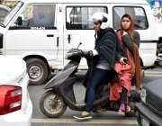 لاہور، دو لڑکیاں سکوٹی پر بیٹھ کر اپنی منزل کی جانب جا رہی ہیں۔