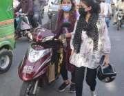 لاہور، لڑکیاں خراب ہونے والی سکوٹی کو ورکشاپ لے کر جا رہی ہیں۔