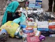 لاہور، ایک بزرگ محنت کش خاتون عینکیں فروخت کرنے کیلئے بیٹھی ہے۔