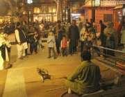 لاہور، فوڈ سٹریٹ میں آئے شہری بندر کا تماشہ دیکھ رہے ہیں۔