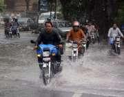 لاہور، شہری بارش کے دوران اپنی منزل کی جانب گامزن ہیں۔