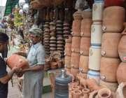 لاہور، ایک شہری مٹی سے تیار کیا جانے والا پانی والا کولر خرید رہا ہے۔