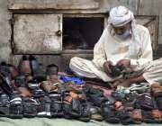 لاہور، ایک موچی جوتے سلائی کر رہا ہے۔