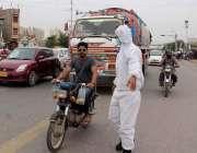 کراچی، کورنگی روڈ پر ٹریفک پولیس اہلکار کورونا وباء سے بچاؤ کیلئے احتیاطی ..