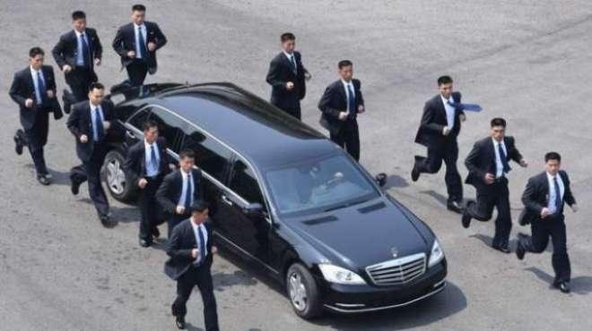 سنگاپور میں شمالی کوریا کے سربراہ کم جونگ اٴْن کی گاڑی کے گرد دوڑتے ..