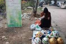 اسلام آباد میں سڑک کنارے فٹ بال فروخت کرنے والی خاتون کی تصویر وائرل