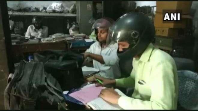 بھارتی دفتر میں ملازمین نے چھت گرنے کے ڈر سے سر کی چوٹ سے بچنے کے لیے ..